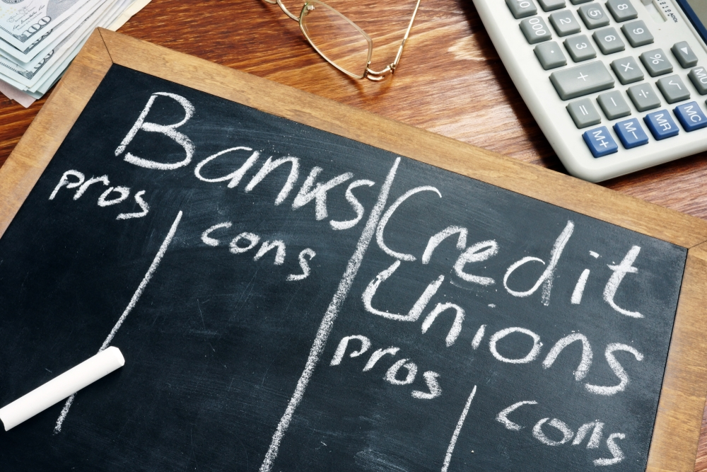 blackboard listing the pros and cons of a credit union over a big bank