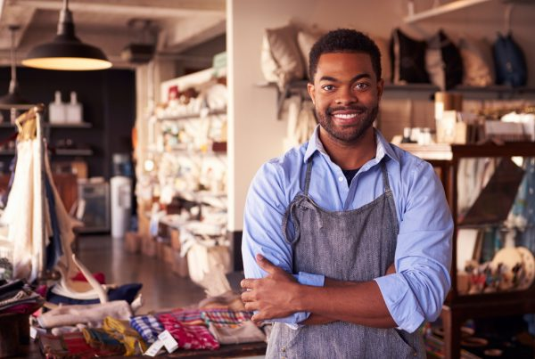small business owner standing in his gift shop with arms crossed