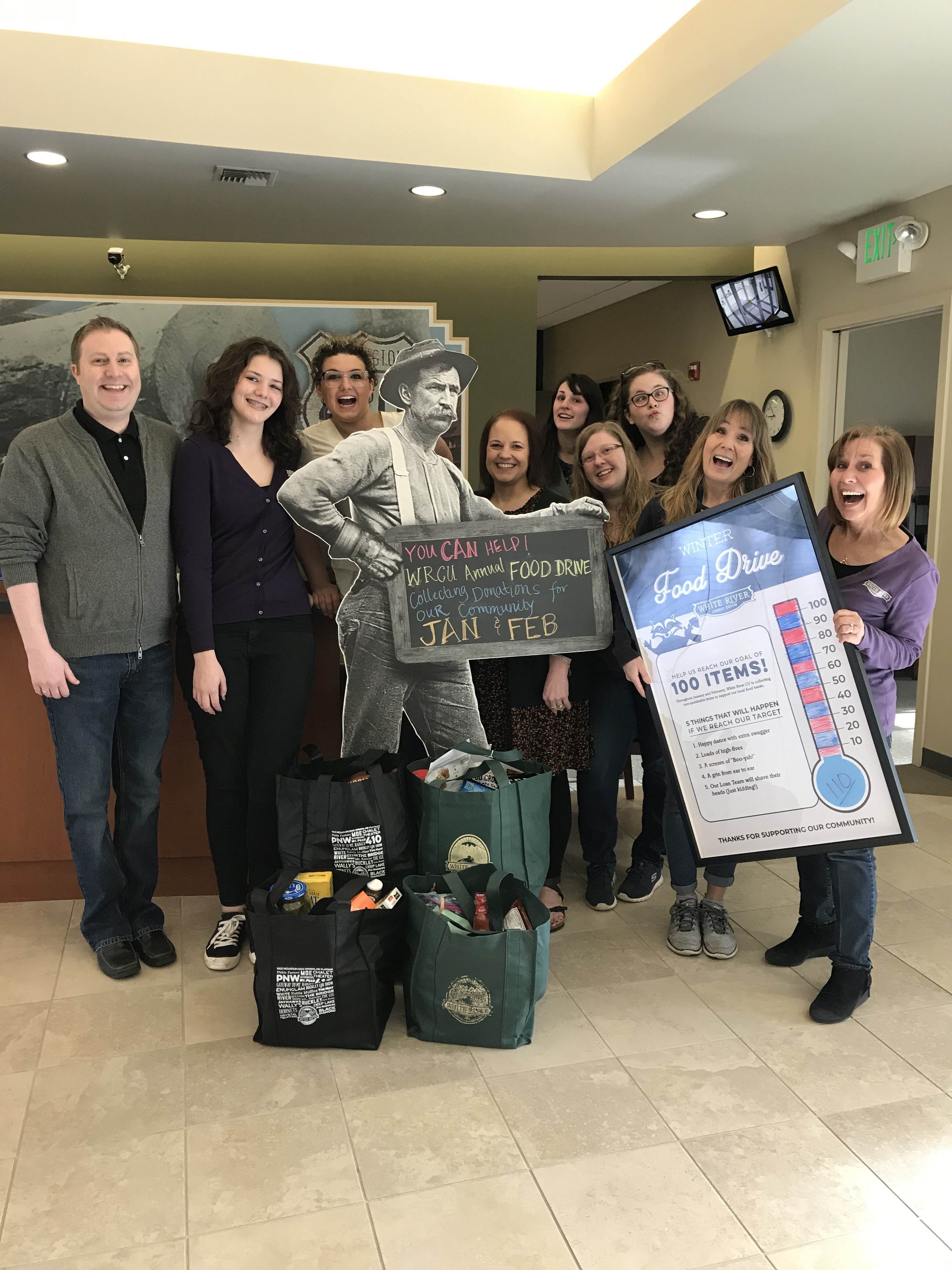 "9 WRCU employees smiling around donated food. One is holding a poster with a count of how many items they have received. A sign can be seen reading ""You can help! WRCU Annual Food Drive collecting donations for our community Jan & Feb"
