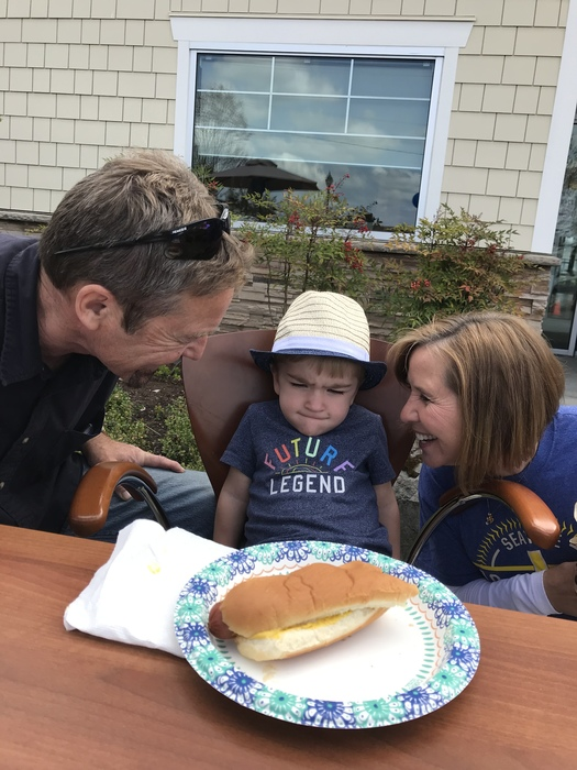 Hot dog on the table, there is a toddler aged boy frowning as two people smile at him from either side
