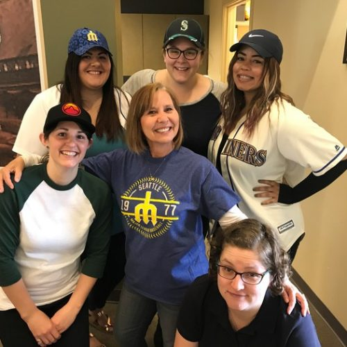 Six WRCU Team members pose smiling for a picture. They are all wearing various baseball style shirts and hats