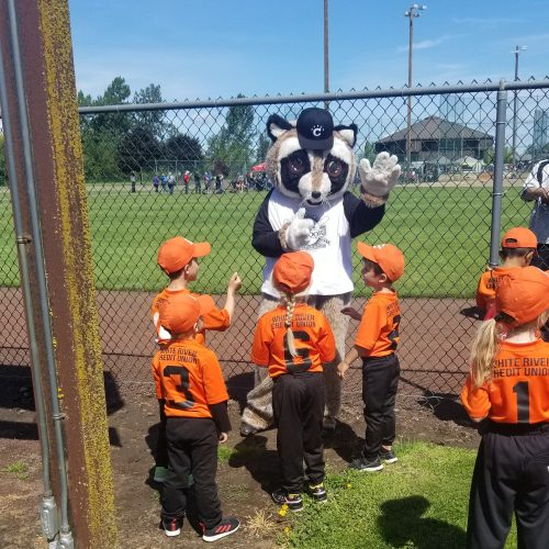 Rocky waving to a group of children in the Chinook Little League