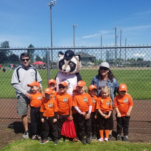 "Rocky posing with a Chinook Little League team. The team is all wearing orange jerseys while Rocky is sporting a baseball tee that says ""Chinook Little League"""
