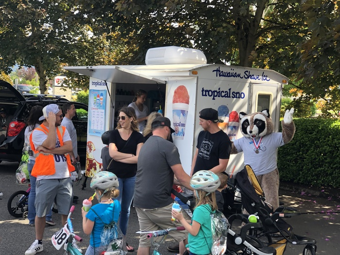 Rocky Raccoon standing next to an Hawaiian Shave Ice truck with kids on bikes and adults in front of him