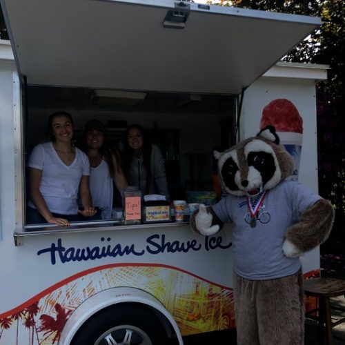 Rocky Racoon standing next to a Hawaiian Shave Ice truck giving a thumbs up