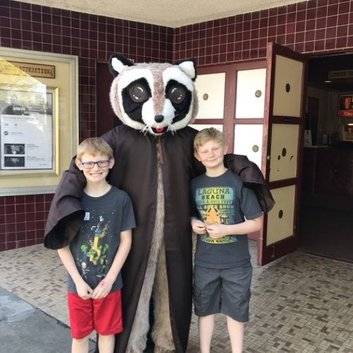 Rocky Raccoon posing with two boys in front of Chalet Theater