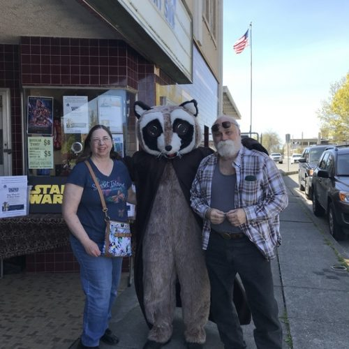 Rocky Raccoon posing with man and woman outside Chalet Theater