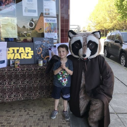 Rocky Raccoon posing with boy in front of Chalet Theater