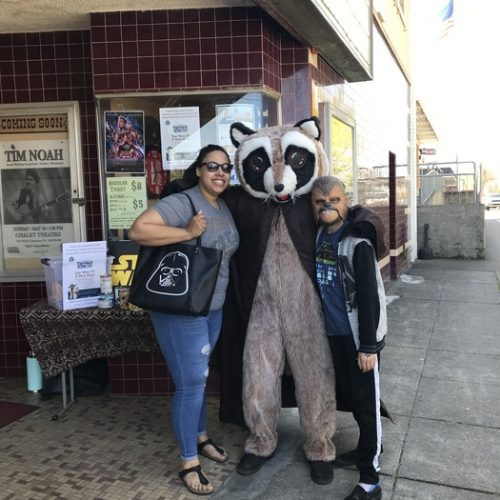Rocky Raccoon posing with a woman and a boy dressed as Chewbacca