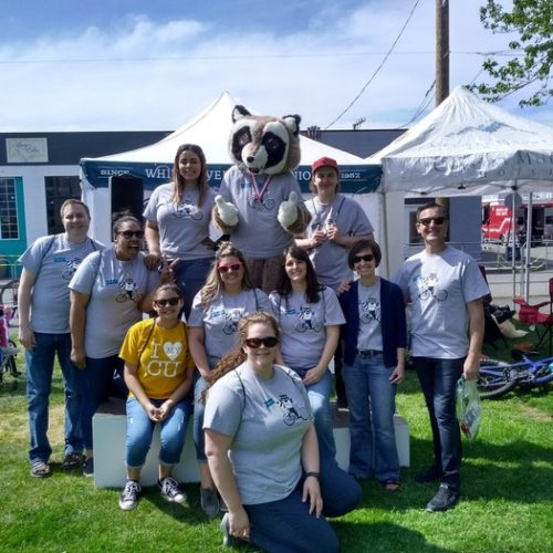 White River CU team posing with Rocky Raccoon. All of them are wearing White River t-shirts