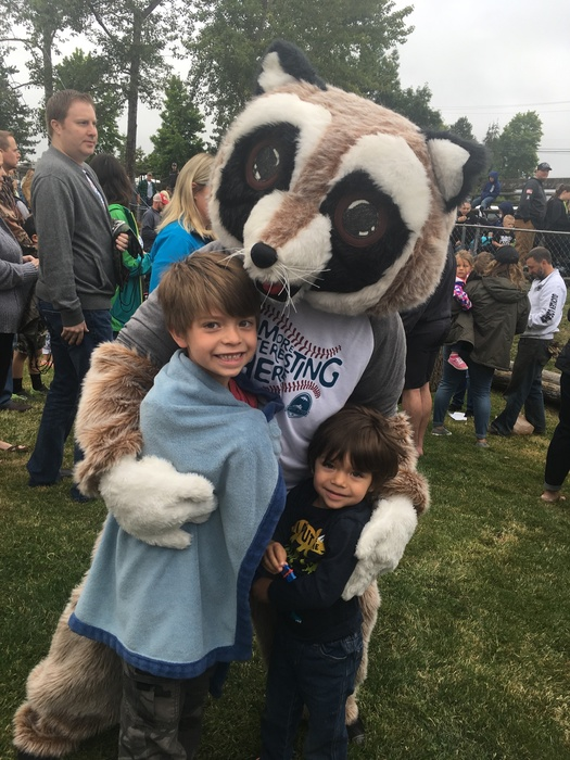 Rocky Raccoon hugging two young boys