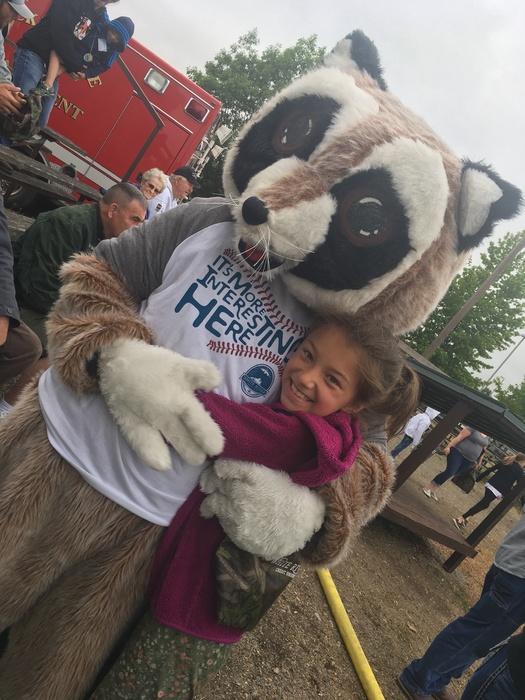 Rocky Raccoon side-hugging young girl