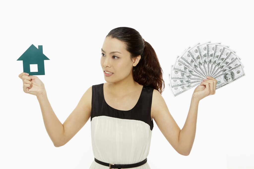woman holding up a paper house and cash representing a Home Equity Line of Credit