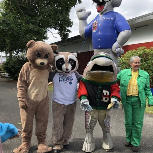 Rocky Raccoon poses with people in costumes: a bear, a shark, and a corn on the cob