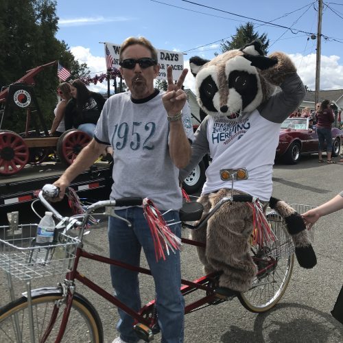 Man on tandem bicycle showing the peace sign with Rocky Raccoon in the back saluting