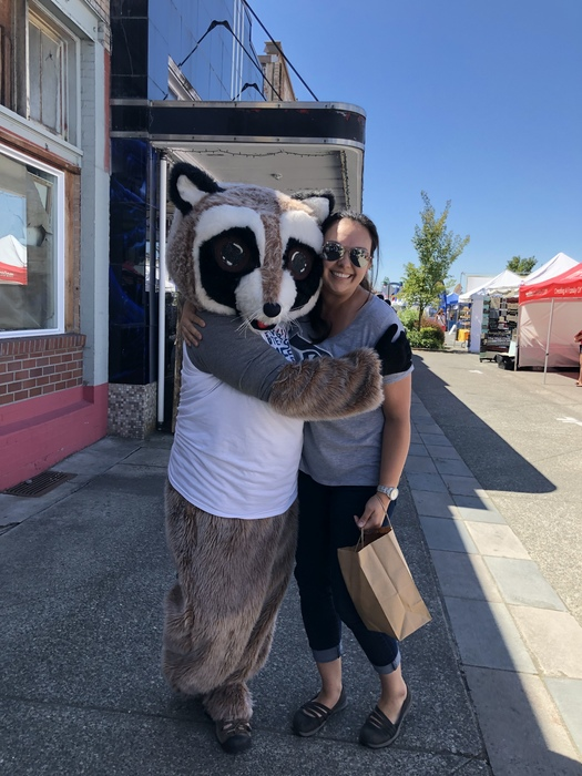 Rocky Racoon hugs woman holding paper bag