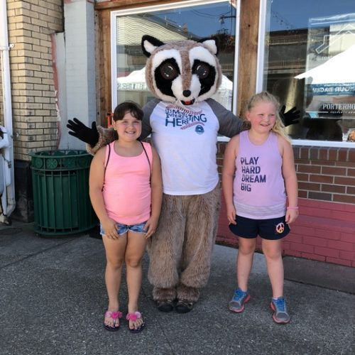Rocky Raccoon poses with two young girls in shorts. Standing in front of a building