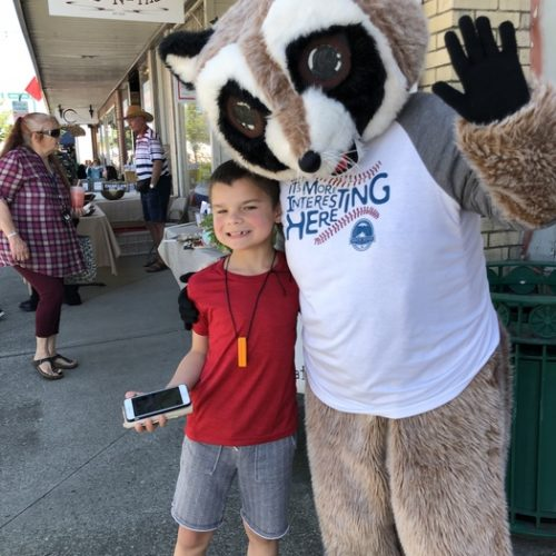 Rocky Racoon side hugs young boy holding cellphone