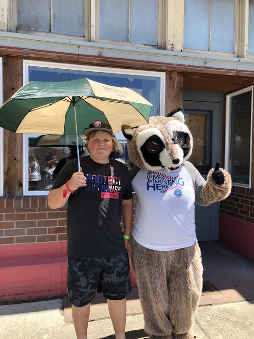 Rocky Raccoon side hugs young boy holding WRCU umbrella above his head, blocking them from the sun
