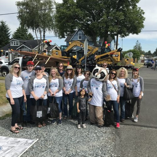 "Rocky Raccoon posing with White River Credit Union staff before the Buckley Log Show Parade. They are all wearing baseball shirts stating ""It's more interesting here"""