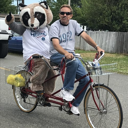 Man riding a tandem bicycle with Rocky Raccoon in the back giving a thumbs up