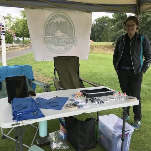 A WRCU rep stands under on a golf coursea tent next to a table that has various SWAG items on it for golfers.