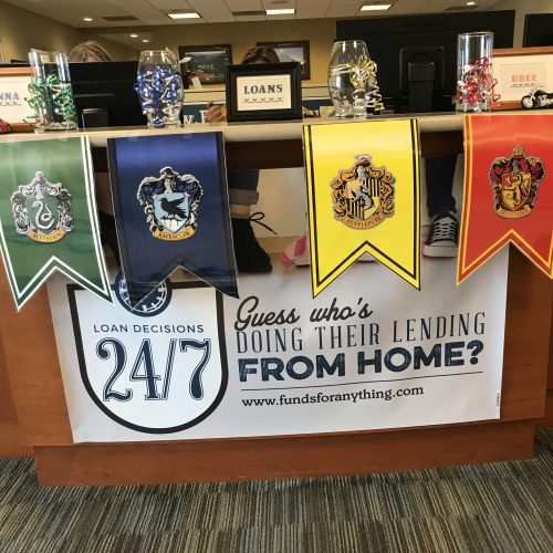 Banners of each Hogwarts house hang from the front counter of WRCU