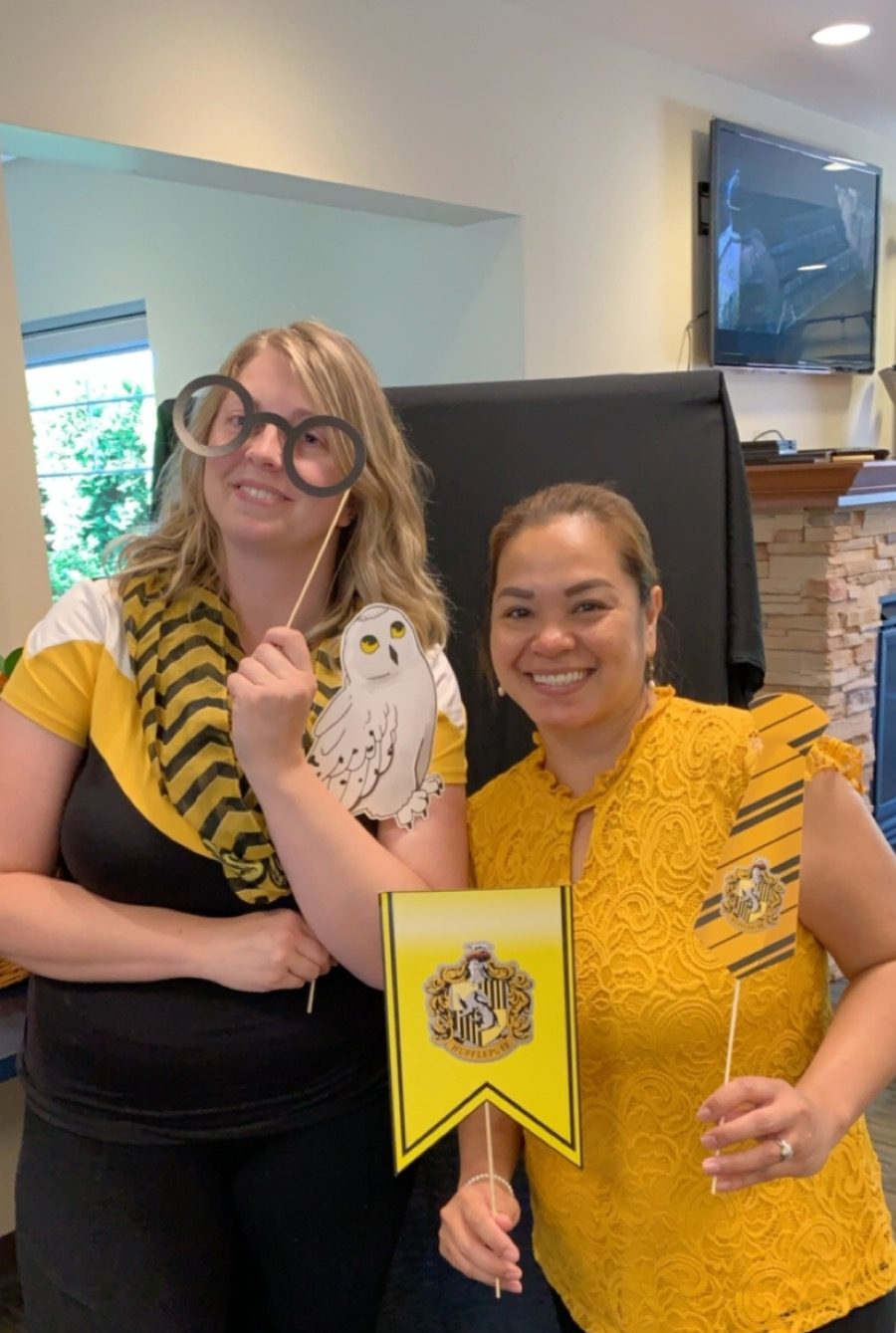 Two women wearing yellow and holding a Hufflepuff banner as well as prop glasses and a prop white owl