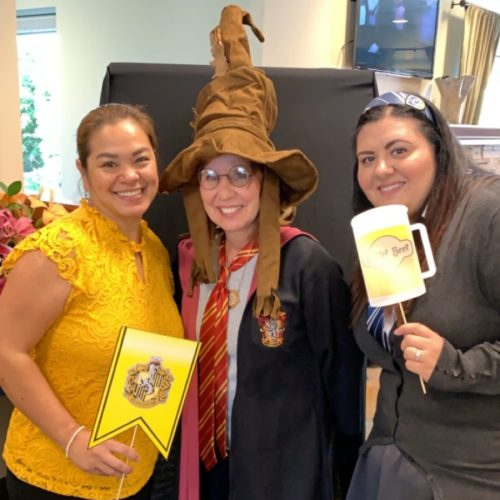 Three women dressed in Harry Potter themed attire pose with Ravenclaw banner and butter beer prop