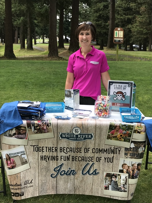"WRCU Rep standing behind a table filled with golfing swag, candy, and a sign reading ""Join Us"""