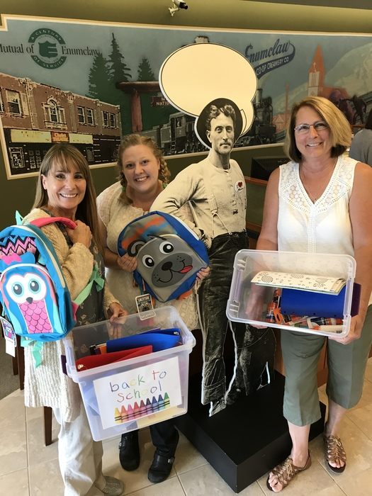 WRCU employees pose holding school supplies to donate to the Enumclaw school district