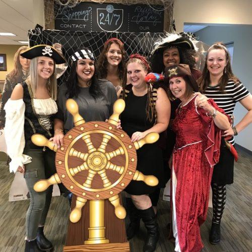 WRCU employees dressed as pirates behind pirate wheel