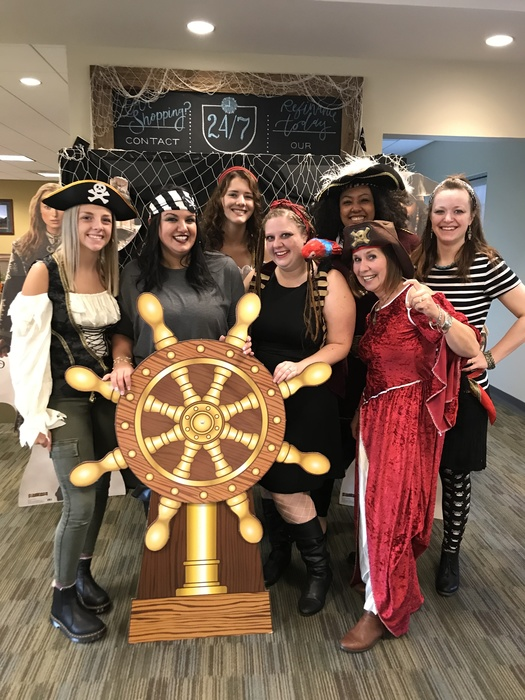 WRCU employees dressed as pirates behind pirate wheel