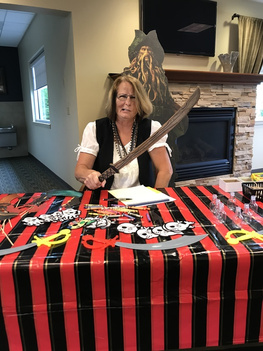 WRCU employee posing at a decorated table dressed like a pirate holding a knife