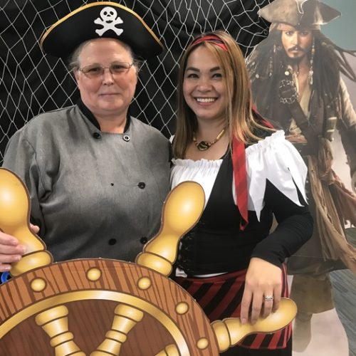 WRCU employees posing in front of pirate wheel dressed like pirates