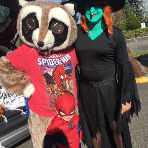Rocky and community member posing in Halloween costumes at MRCC MOPs Annual Trunk or Treat