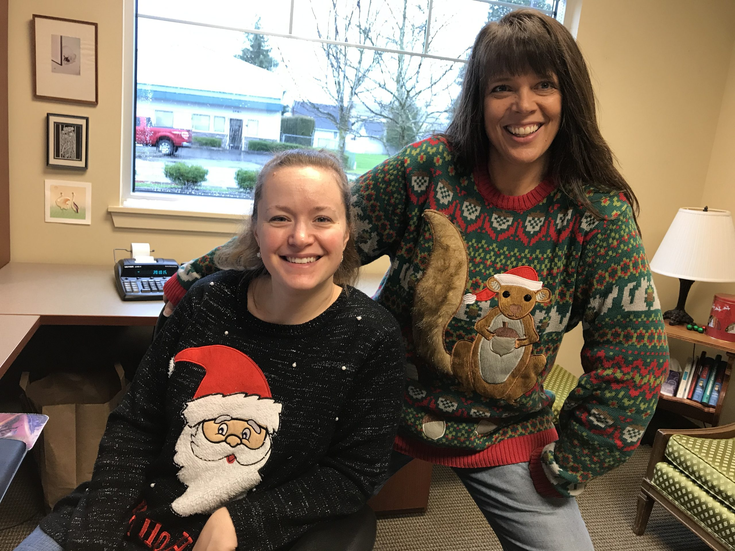 Two WRCU employees posing in their ugly sweaters
