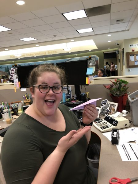 WRCU employee holding a paper airplane