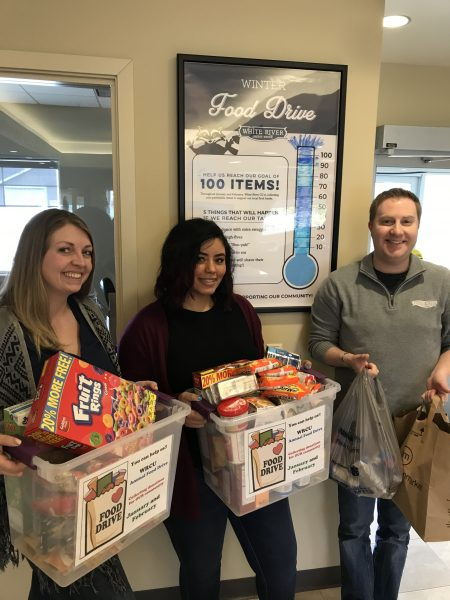 White River Credit Union employees holding food drive items