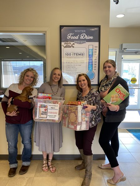 White River Credit Union Employees holding food drive items with a dog