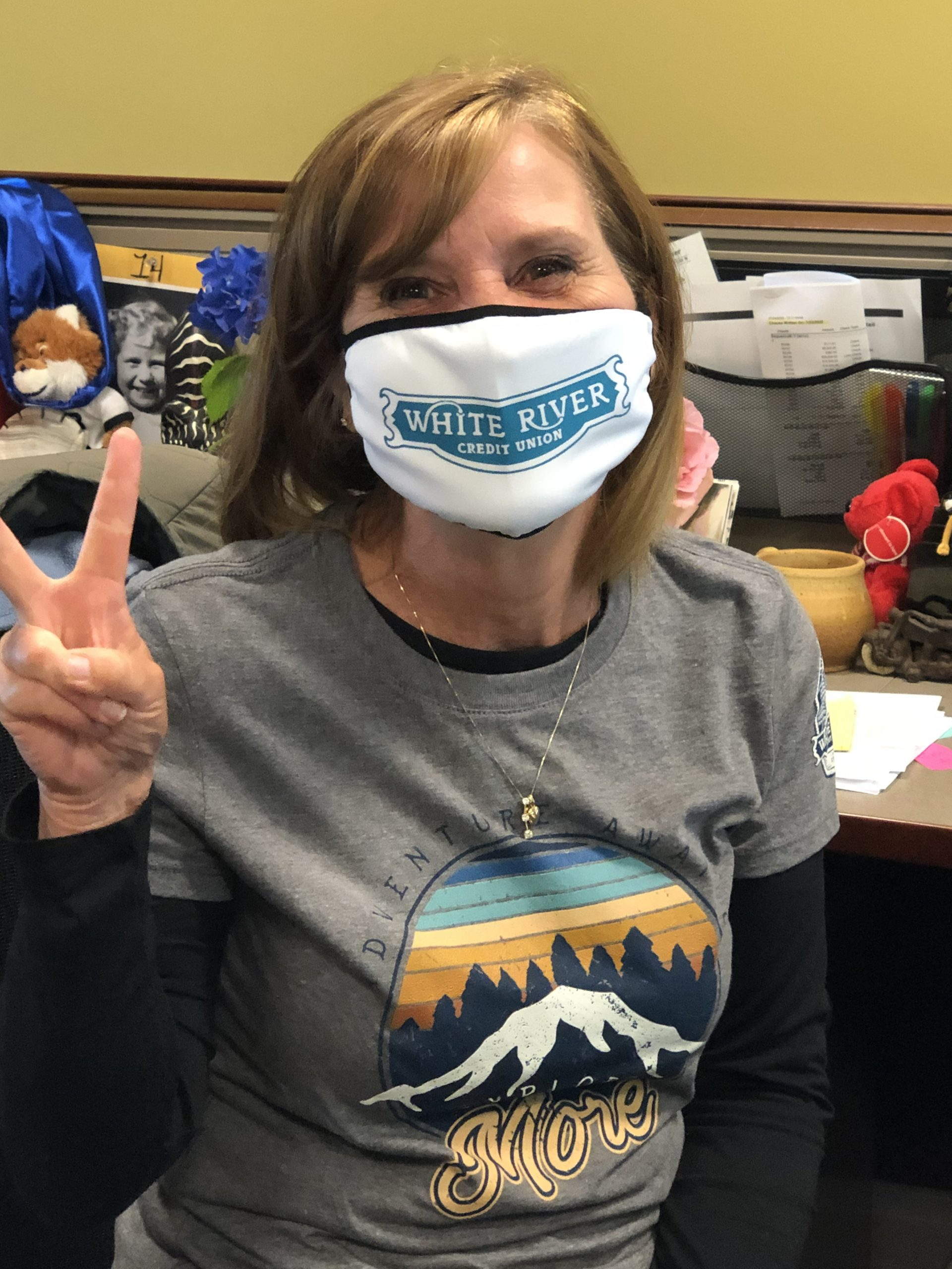 White River Credit Union employee making a peace sign and wearing mask