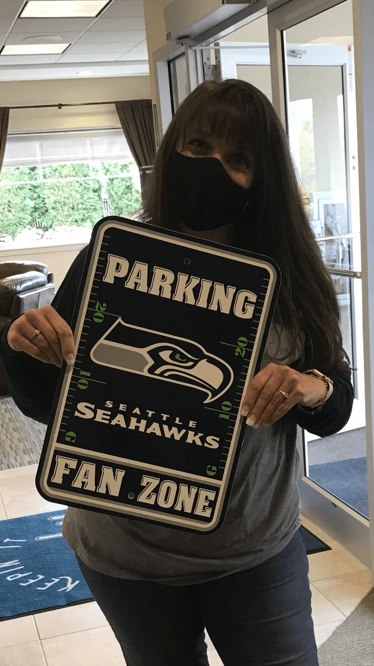 Yvette holding Seahawks Fan Zone sign