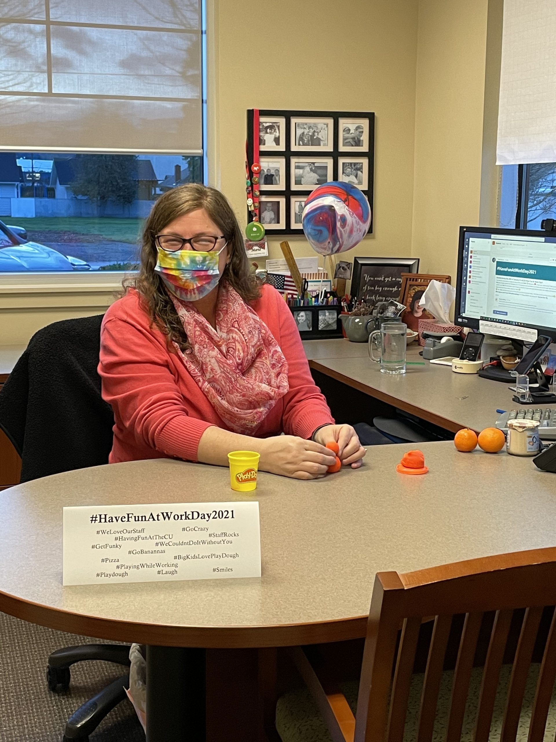 Credit union employee at desk on national have fun at work day