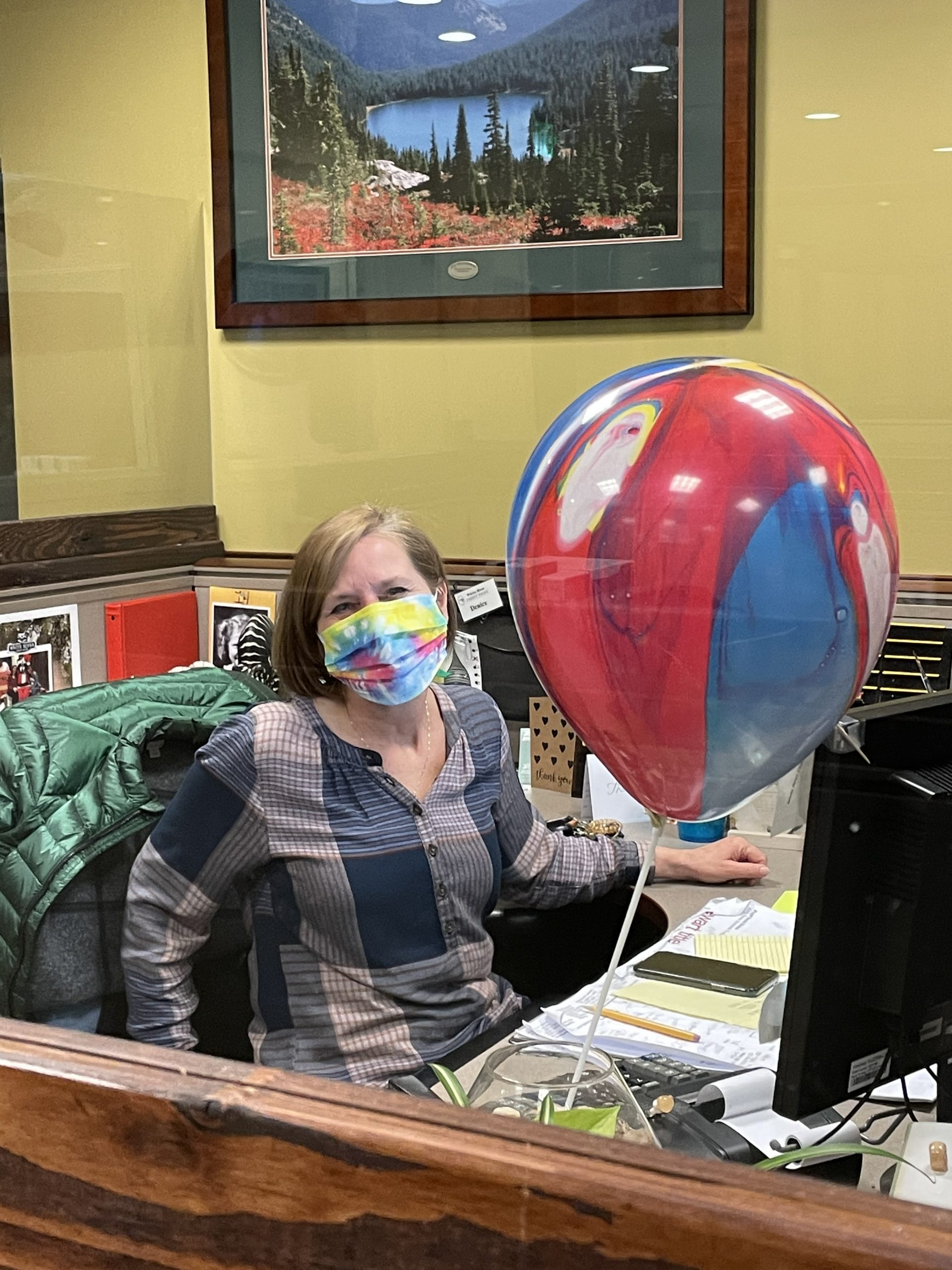 Credit union employee at desk with balloon and mask, on national have fun at work day